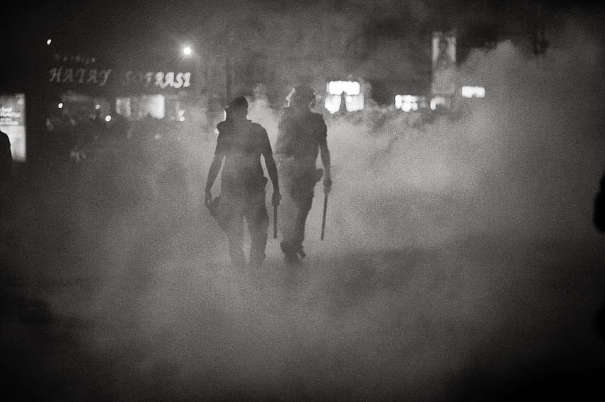 Riot police officers patrols the streets overcasted by thick clouds of tear gas