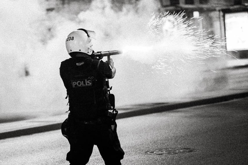 Riot police officer fires a tear gas canister disrepsect of the safety standards (45° lining of gunmetal). Istanbul