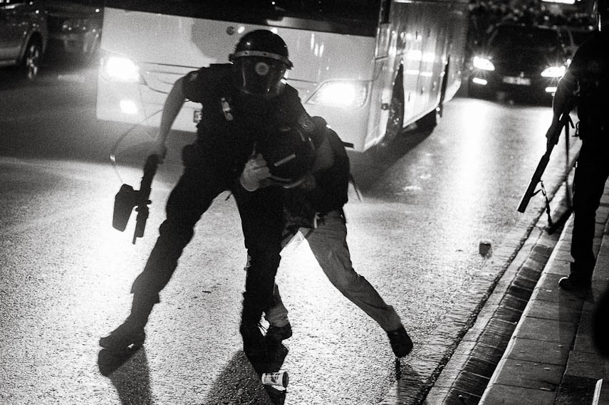 A demostrator is being roughly dragged by a riot police officer during the night. Istanbul 16/06/2013