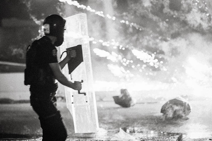 A riot police officer shield himself from firecrackers. Istanbul, 16/06/2013