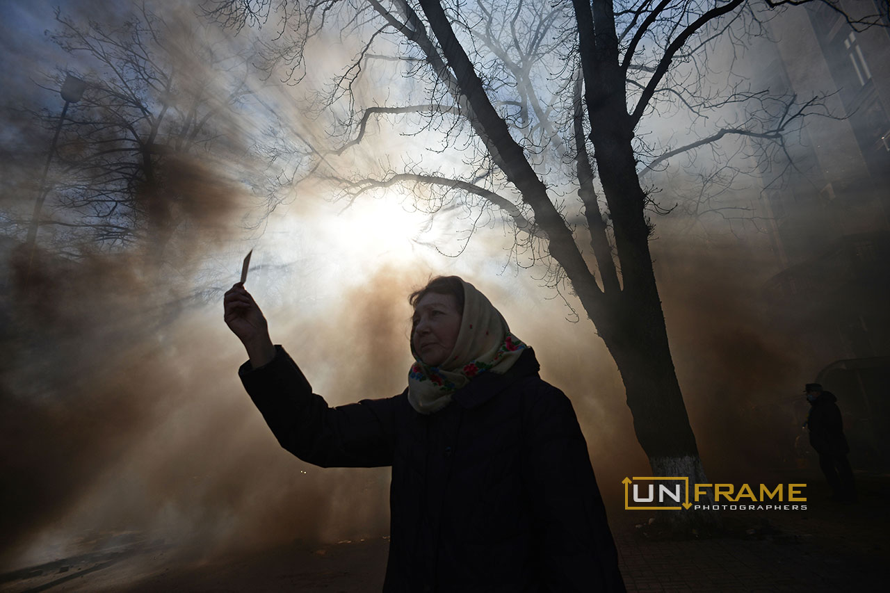 A woman protests under a thick cloud of smoke. Kiev, Ukraine