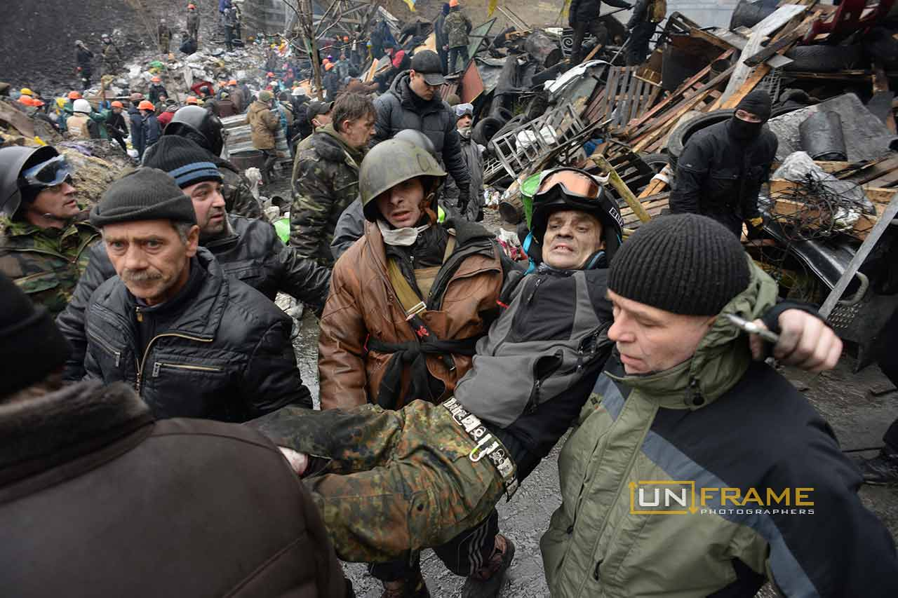 Protesters help wounded people, lift and bring them to a makeshift clinic where red cross medics treat them as they can do. Kiev, Ukraine