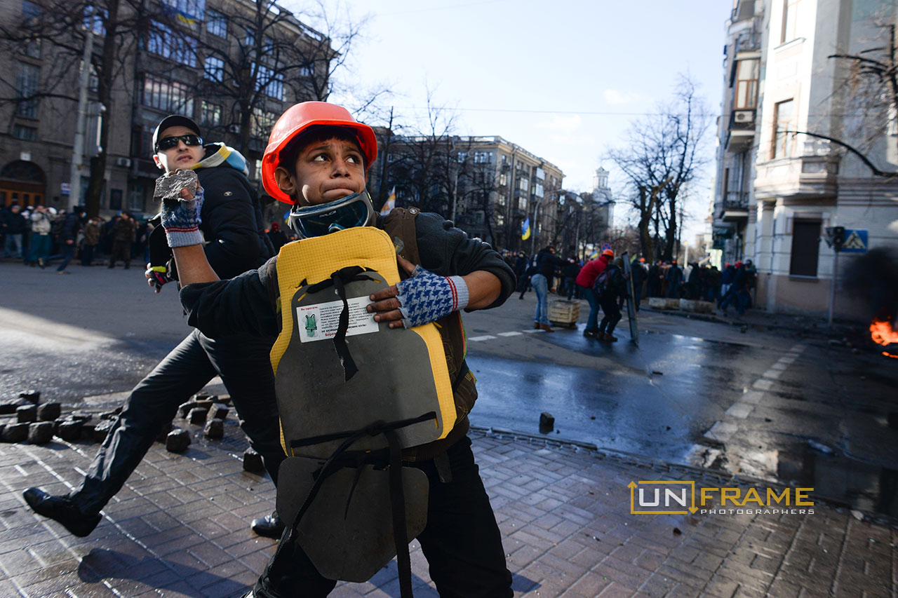 A young kid protester hurls paving stones and takes part into the violent protest. Kiev, Ukraine