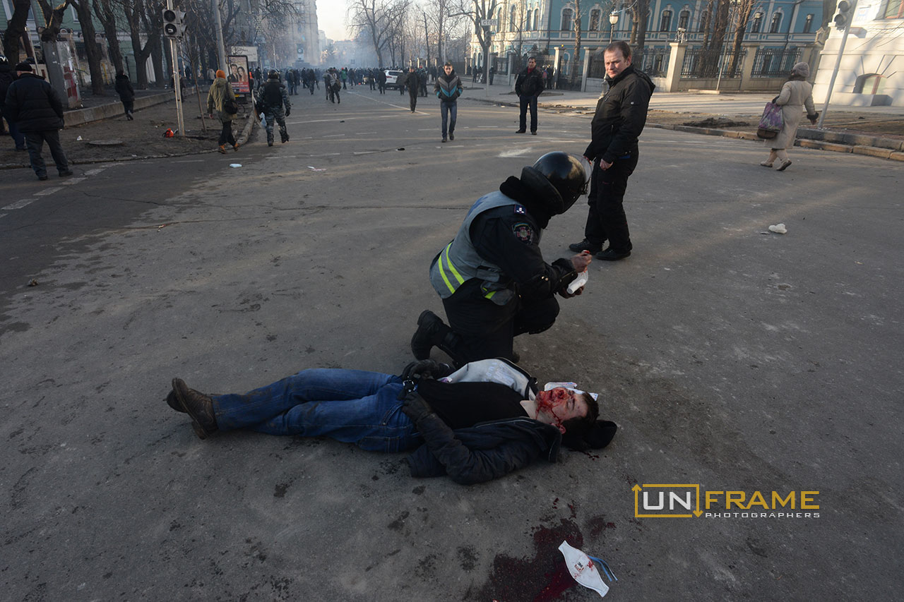 A policeman provides first aid to a wounded protester who fell on the field. Kiev, Ukraine