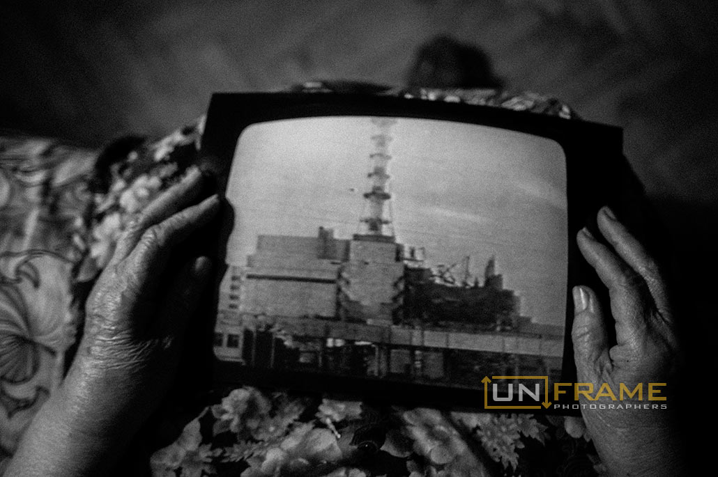 An elderly woman - witness of the Chernobyl catastrophe holds the picture of the 4th reactor of the the Chernobyl nuclear power plant after devastation - Photo: Mstyslav Chernov / UnFrame