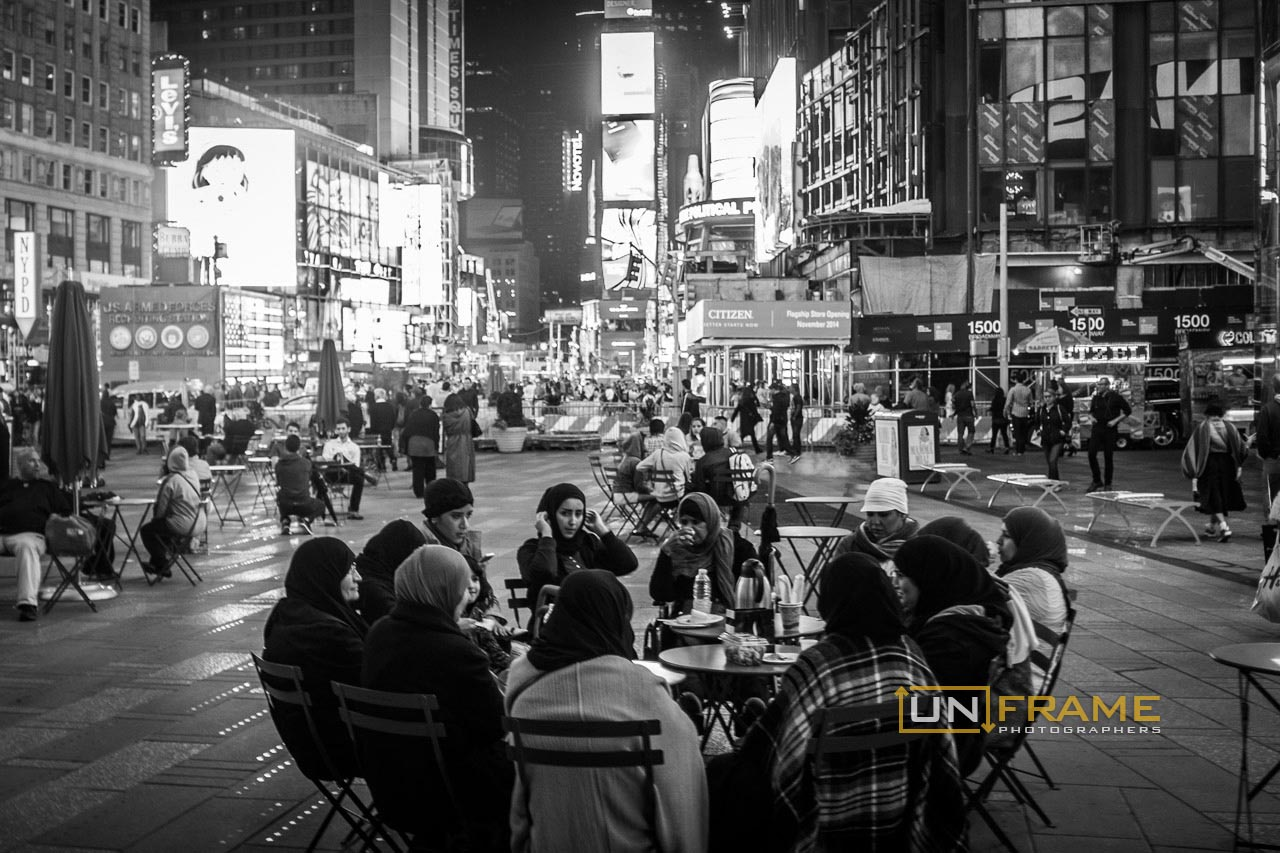 Muslim women in their typical clothing share their meal in Time Square.