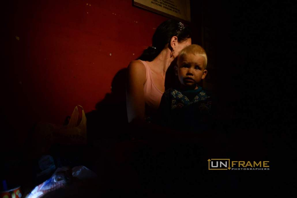 Mother and her child hiding in an old Soviet Union bomb shelter during shelling. Donetsk, Eastern Ukraine